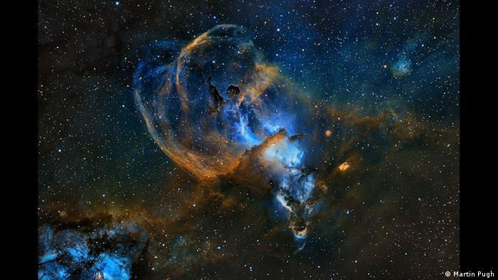 Dunkler Kosmos mit vielen kleinen hellen Punkten und blau-orangefarbenen Wolken (Foto: Martin Pugh).