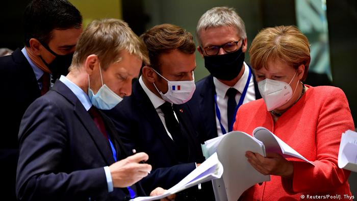 Spain's Prime Minister Pedro Sanchez, France's President Emmanuel Macron and German Chancellor Angela Merkel look into documents