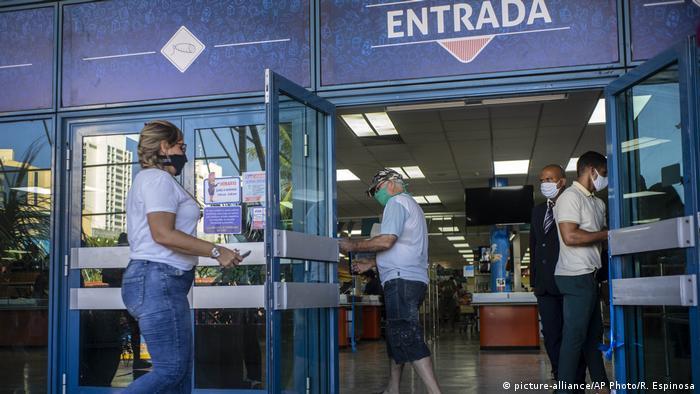 Menschen mit Gesichtsmaske betreten einen Supermarkt