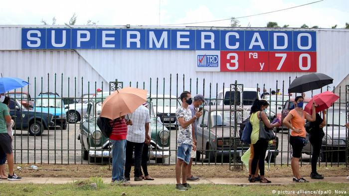 Shoppers lining up in front of a Cuban supermarket where payments in US dollars are accepted