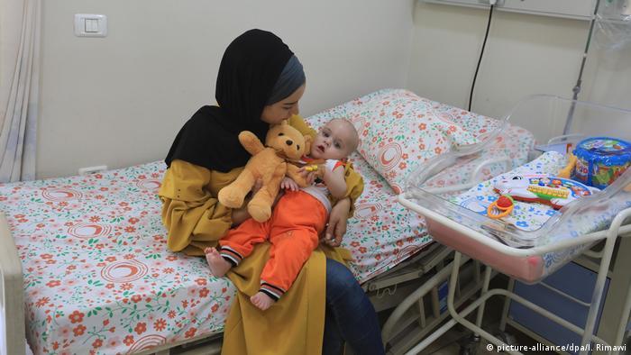Eine junge Frau mit Kopftuch sitzt auf einem Krankenhausbett und hält ein Kind und dessen Kuscheltier im Arm