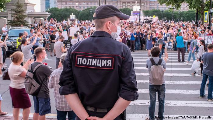 Сотрудник полиции наблюдает за шествием в поддержку бывшего губернатора Хабаровского края Сергея Фургала в Хабаровске, 21 июля 2020 года.
