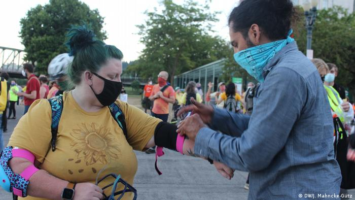A man helps to tie elbow pads around the arms of another protester for protection