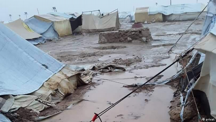 Tents stand on muddy ground covered in puddles