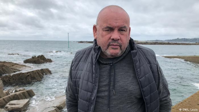 A man wearing a black coat looks into the camera with the sea behind him