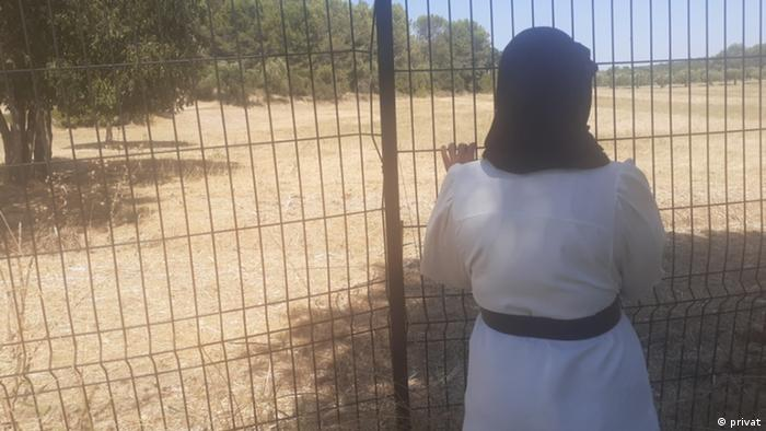 Sara faces away from the camera and looks through a wire fence