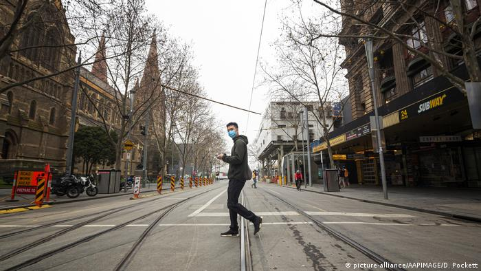 Man crosses the street in an empty Melbourne street during lockdown