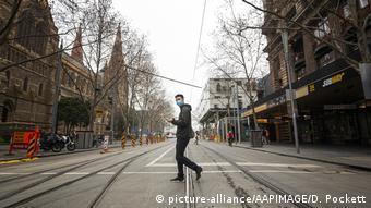 Мужчина в маске переходит улицу в Мельбурне