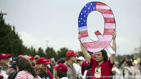 A Trump supporter holds a Q sign at a rally in Pennsylvania