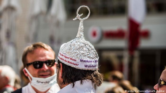 A man walks around with an tinfoil hat with slogans that decry the need for masks during the coronavirus pandemic