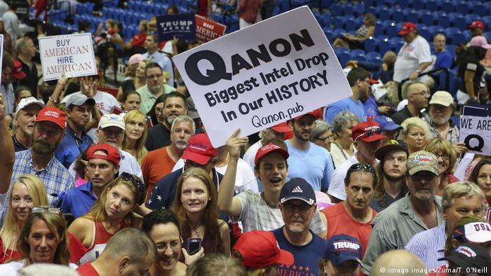 Pessoas seguram cartazes com símbolos e slogans do QAnon em evento de campanha de Donald Trump