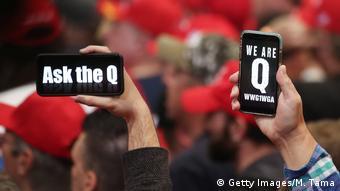 Двое мужчин держат мобильные телефоны, на экранах которых написано по английски: Спроси Q и Мы Q