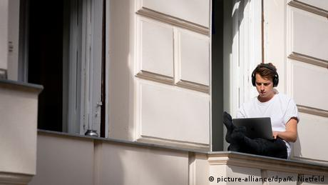 A young man with a computer in his lap sitting on the window sill of a tenant house in Berlin