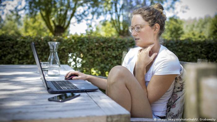 Mulher sentada à mesa usa um computador