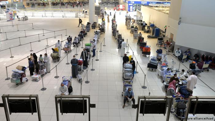 Egyptian passangers form a long queue in an airport departure lounge ahead of a repatriation flight