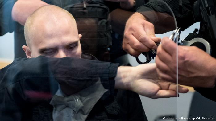 Stephan B., his face covered by his arm, being handcuffed by police