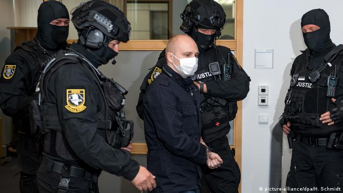 Handcuffed Stephan B. being led into court by four policemen in riot gear (picture-alliance/dpa/H. Schmidt)