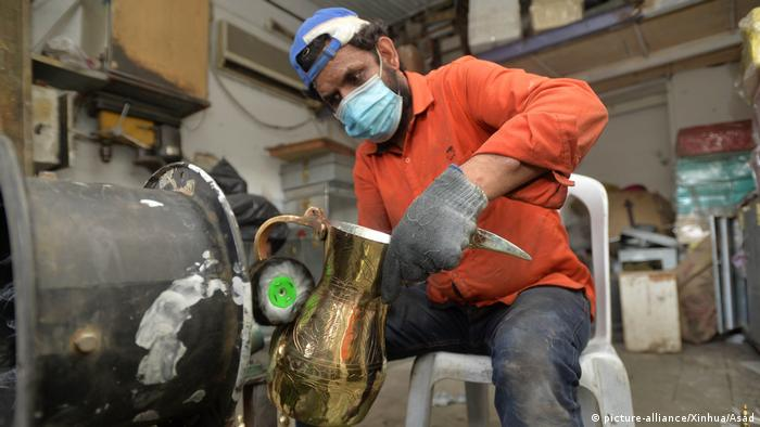 A worker wearing a mask polishes a gold coffee pot into a shine