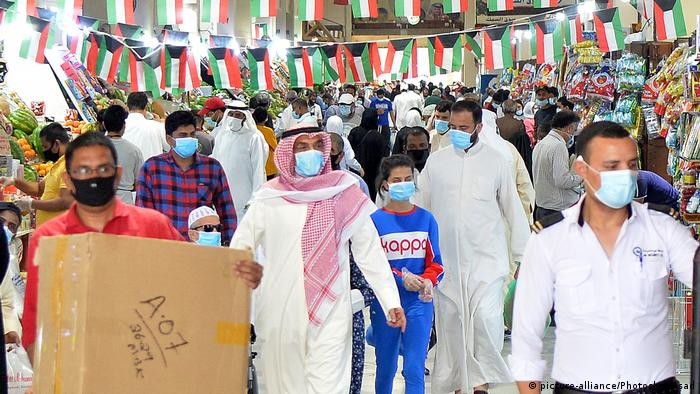 Shoppers walk around in masks under bunting with the flag of Kuwait in a market in Kuwait City