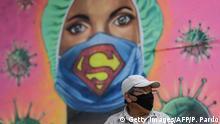 Ein Coronavirus Graffito an einer Wand in Mexico. Davor ein Mann mit Maske. (Getty Images/AFP/P. Pardo)