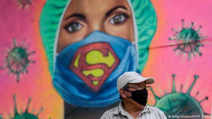 Граффити: женщина-медик в хирургической шапочке и маске с символом супермена. На фоне граффити стоит мужчина в защитной маске.