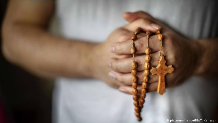 Foto simbólica de unas manos con un rosario de madera.