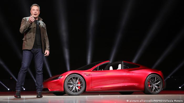 Elon Musk stands in front of Tesla Roadster