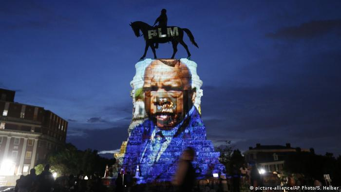 An image of the late civil rights leader and congressman John Lewis is projected onto the statue of Confederate Robert E. Lee in Richmond, Virginia