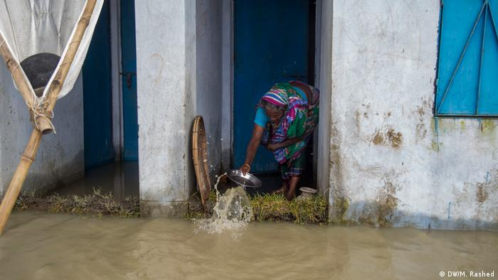 A woman scoops up water and throws it back on the street using a silver pan