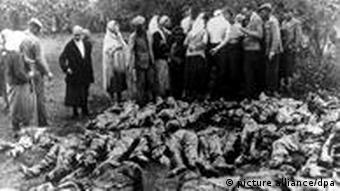 Menschen stehen vor einem der freigelegten Massengräber von Katyn (Foto: dpa)