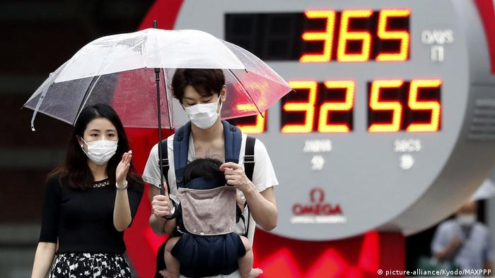 Two people crossing the street holding an umbrella in Tokyo
