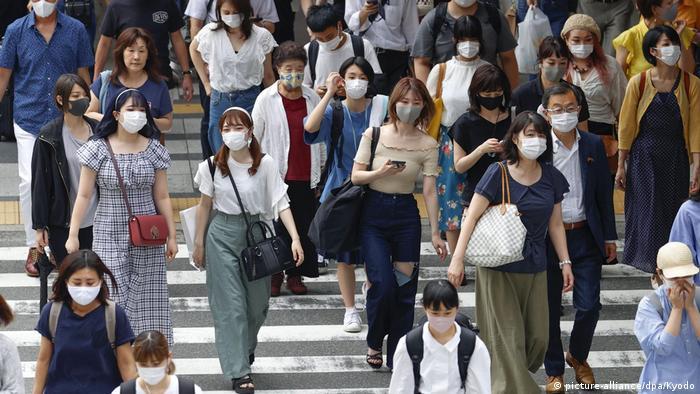 Pessoas andam de máscara em rua no Japão