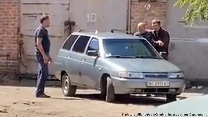 In this handout video grab released by Ukrainian Criminal Investigations directorate, a criminal suspect, right, is taking a hostage in Poltava, Ukraine. On July 23, a man whom police officers tried to detain for stealing a car, was threatening to detonate a grenade and took a senior Ukrainian policeman hostage in the central city of Poltava. (picture-alliance/dpa/Criminal Investigations Department)