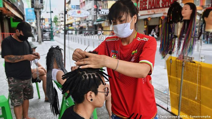A woman teases hair into dreadlocks for a customer at Khao San Road, empty of tourists due to the restrictions on entry by foreigners into Thailand due to the COVID-19 novel coronavirus, in Bangkok