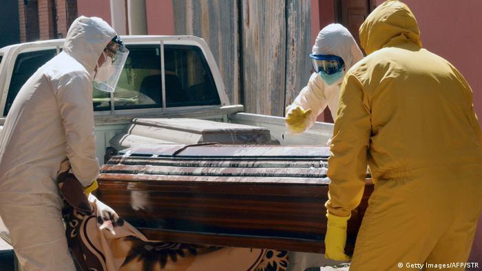 Мужчины в защитных костюмах несут гроб в боливийском Сан-Хосе