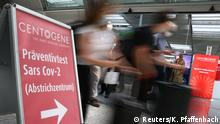 Travellers rush past the entry of Germany's first walk-through the coronavirus disease (COVID-19) test center which is opened by diagnostics provider Centogene in cooperation with air carrier Lufthansa and Fraport at the airport in Frankfurt, Germany June 29, 2020. REUTERS/Kai Pfaffenbach