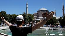 A man gestures as people wait for the beginning of Friday prayers outside Hagia Sophia Grand Mosque, for the first time after it was once again declared a mosque after 86 years, in Istanbul, Turkey, July 24, 2020. REUTERS/Umit Bektas