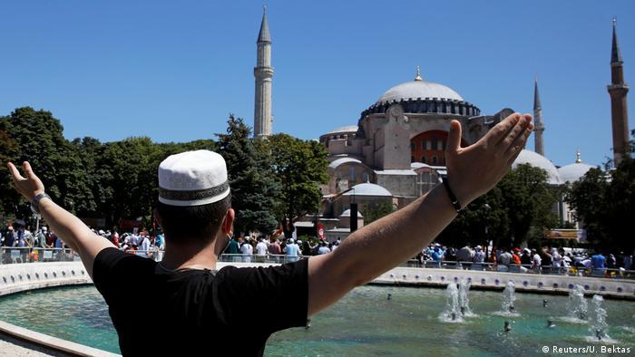 A man gestures as people wait for the beginning of Friday prayers (Reuters/U. Bektas)