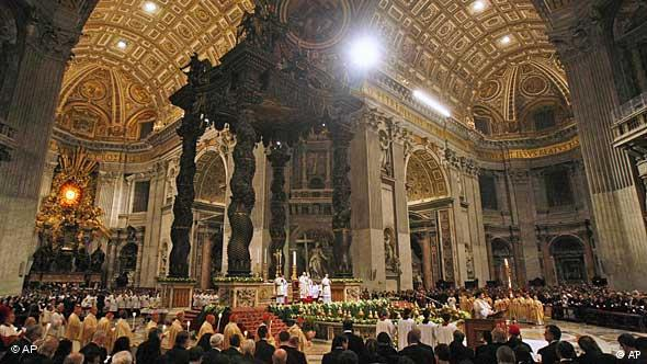 Prelates and the faithful hold candles as Pope Benedict XVI celebrates an Easter Vigil Mass in St. Peter's Basilica at the Vatican