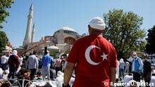 A man wearing a t-shirt with the Turkish flag stands as people wait for the beginning of Friday prayers outside Hagia Sophia Grand Mosque, for the first time after it was once again declared a mosque after 86 years, in Istanbul, Turkey, July 24, 2020. REUTERS/Umit Bektas