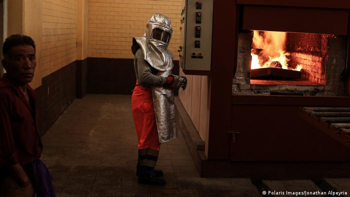 A crematorium worker wearing a silver protective suit stands next to the flames