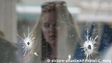 A woman looks at the bullet holes on the window of IV Deli Mark where Friday night's mass shooting took place by a drive-by shooter on Saturday, May 24, 2014, in Isla Vista, Calif. The shooter went on a rampage near a Santa Barbara university campus that left seven people dead, including the attacker, and seven others wounded, authorities said Saturday. Attorney Alan Shifman says the family of a man suspected in the shooting rampage called police several weeks ago after being alarmed by YouTube videos regarding suicide and the killing of people. Shifman is the attorney for Peter Rodger, who was an assistant director on The Hunger Games film series. Authorities have not confirmed the identity of the shooter. (AP Photo/Jae C. Hong) |
