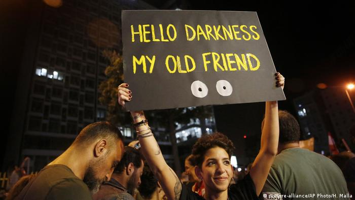 A woman holds a sign above her head which reads 'Hello darkness my old friend'