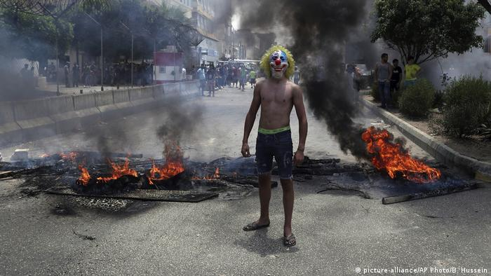 A protester in a clown mask stands in front of a burning blockade