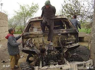 Afghans inspect a burned out German military vehicle at the site where three German soldiers were killed in a firefight on April 2, in Kunduz province