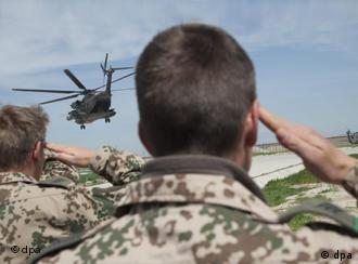 German soldiers salute a departing helicopter in Kunduz