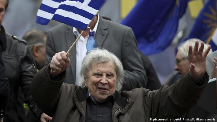 Mikis Theodorakis waves the Greek flag at a rally in Athens in 2018