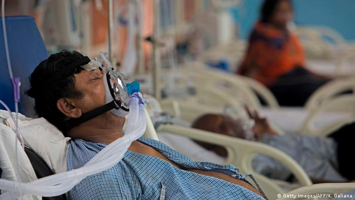 A COVID-19 coronavirus patient lies on a bed at the Intensive Care Unit of the Sharda Hospital, in Greater Noida