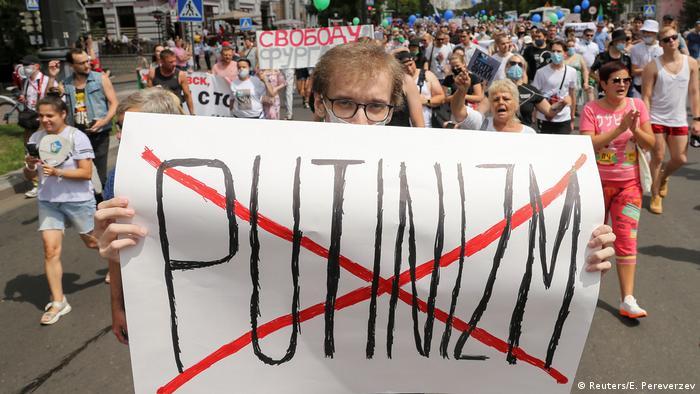 Один из участников протестов в Хабаровске держит в руках плакат, на котором красным крестом перечеркнуто слово Putinizm.