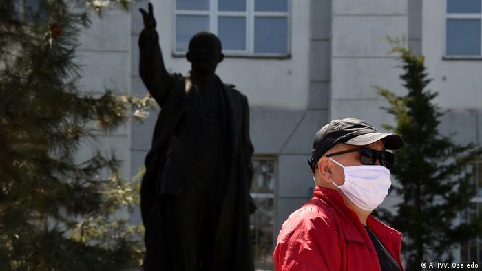 Человек в маске у здания парламента Киргизии